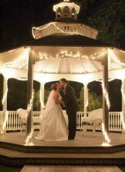 A bride kisses her husband in a veranda at night