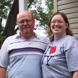 Overjoyed Christian singles from Illinois stand arm in arm while laughing on the porch