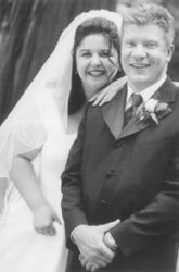 An overjoyed Christian woman lays her arm affectionately on her pleased groom