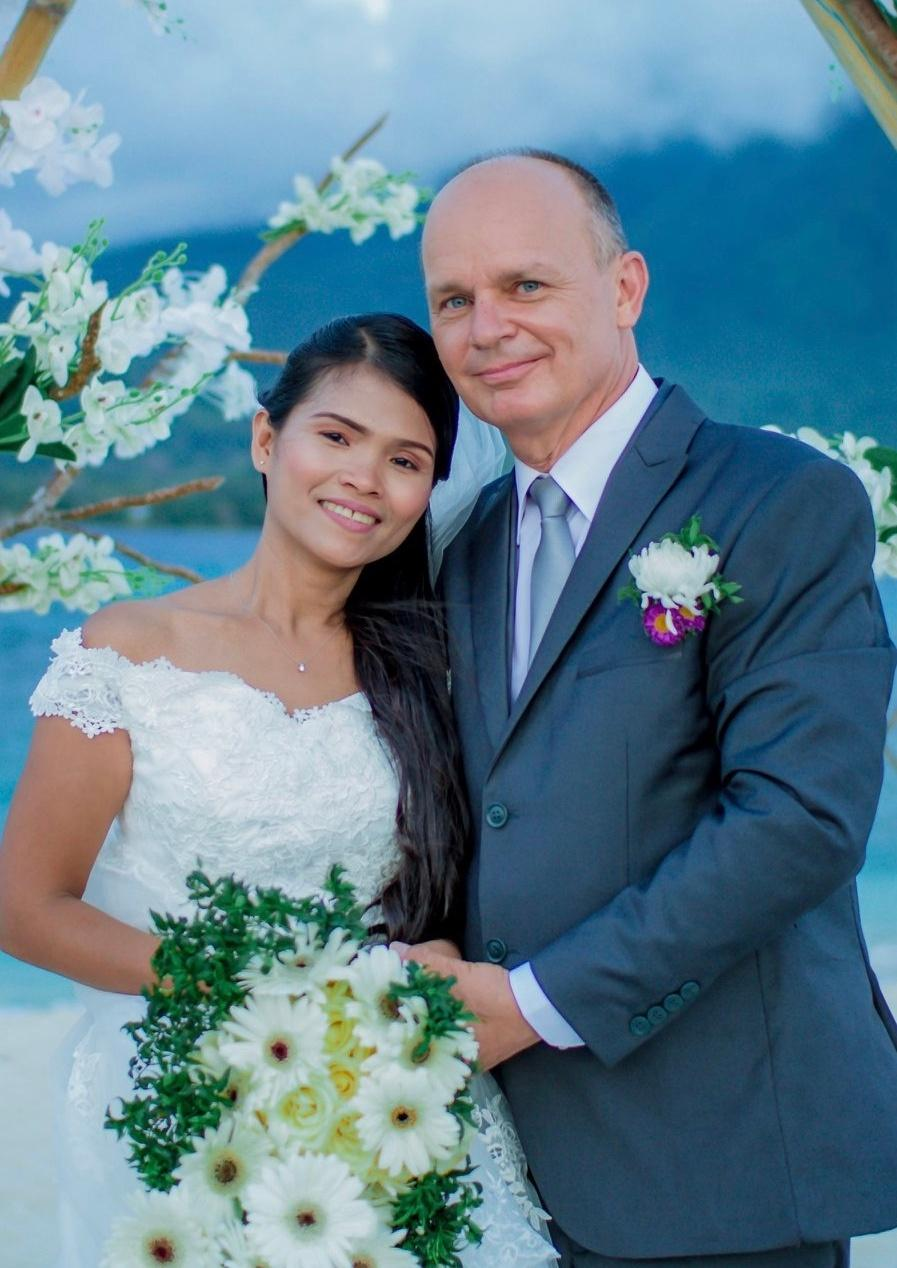 Very happy White man stands next to his East Asian bride who holds bouquet
