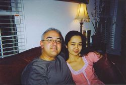 A relaxed man sits on the couch next to a pretty Christian woman