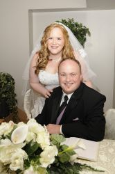 Christian singles from Quebec stand proudly together behind flowers on their wedding day