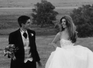 A bride tries running in a field while holding her dress. Husband holds her flowers and laughs