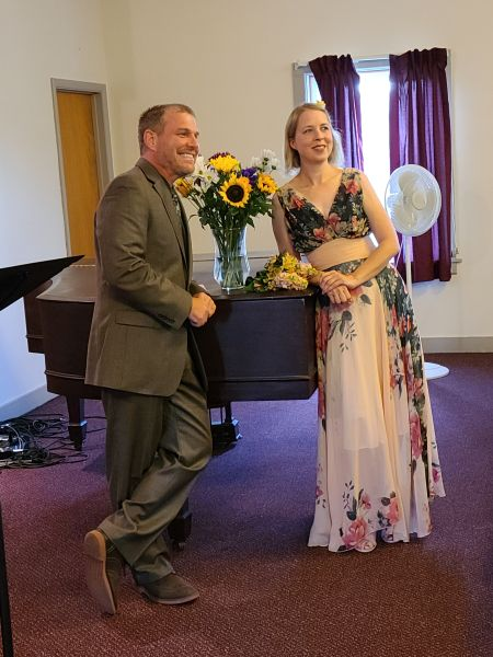 Newlywed Christians posing by piano and smiling