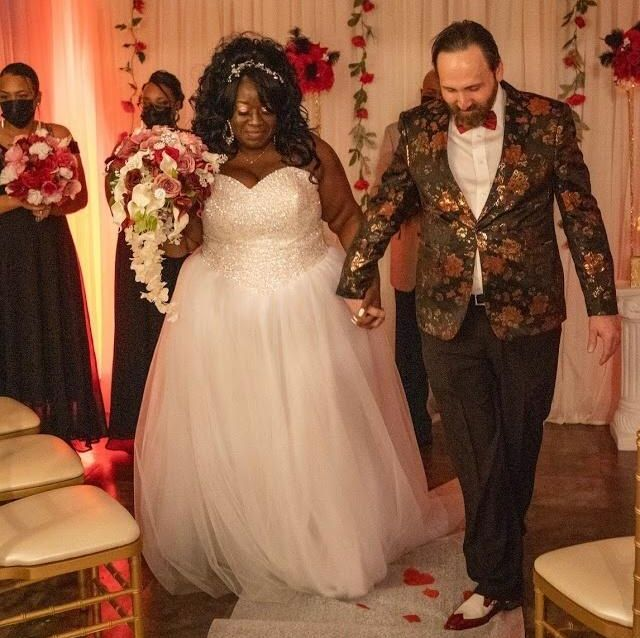 Newlyweds pray together while holding hands at an indoor wedding during COVID