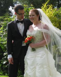 A man stares lovingly at his beautiful red-headed wife on her wedding day
