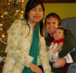 Happy Christian couple with their new baby cuddle on the couch in front of Christmas tree