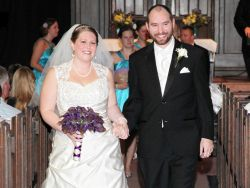 A beautiful bride walks hand in hand with her new husband as churchgoers look at them