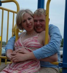 A man holds his fiancee on play structure and laughs