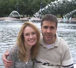 A man hugs a beautiful woman in front of a fountain