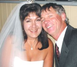 A very joyful looking Christian couple laugh together cheek to cheek just after marrying
