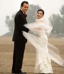 Man catches his wife's dress on a very windy wedding day
