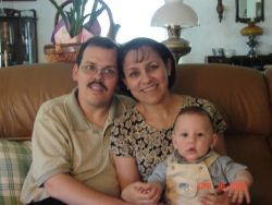 A happily married Christian woman sits with her new baby and her husband