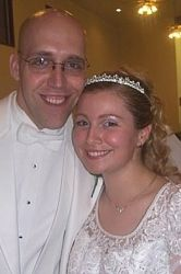 A happy smiling man in a white suit stands next to a beautiful woman in a tiara