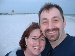 A Christian couple laugh together for a beach selfie