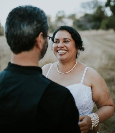 Happiness in a picture as bride giggles uncontrollably while facing husband