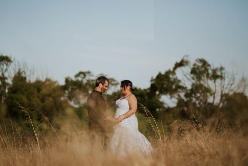 Newlyweds in field talking in background while holding hands
