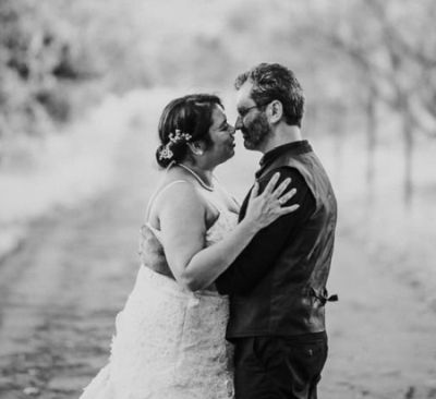 Tree lined shot of married couple embracing