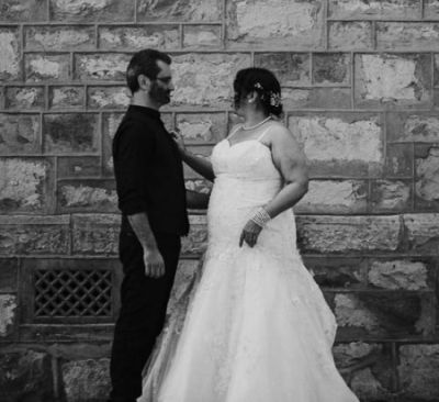 Christian couple wedded outdoors while standing in front of old wall