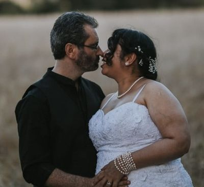 Man holding his Christian bride who is leaning in to kiss him