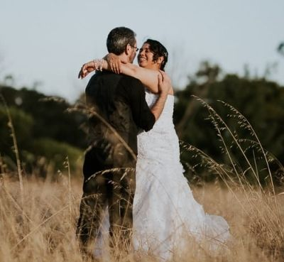 Happy Christian bride laughing while putting arms around husband and smiling