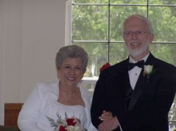 Former Senior Christian single stands next to his new smiling bride