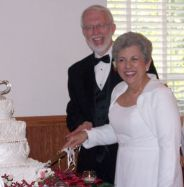 Laughter from the newlyweds as they cut the wedding cake