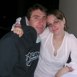 A contented woman in pink holds on to a man in a sweater