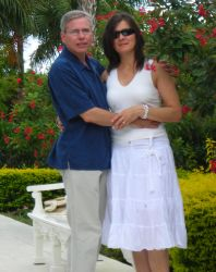 A couple pose together arm in arm in a beautiful garden
