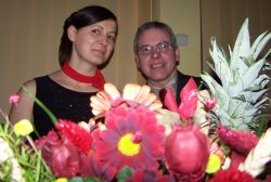 A man laughs while playfully looking over some flowers as he sits next to a beautiful woman