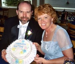 Cross state romance for Christian singles leads to marriage. Man and woman smile as they hold up a unique round wedding cake
