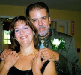 Christian singles no more as a newly married man stands behind his wife, who smiles and holds his hand tenderly
