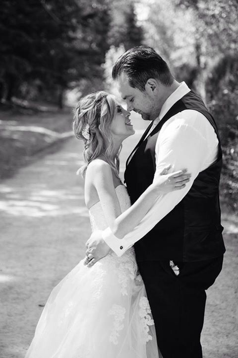 Gorgeous newlywed Christians embrace on tree-lined street