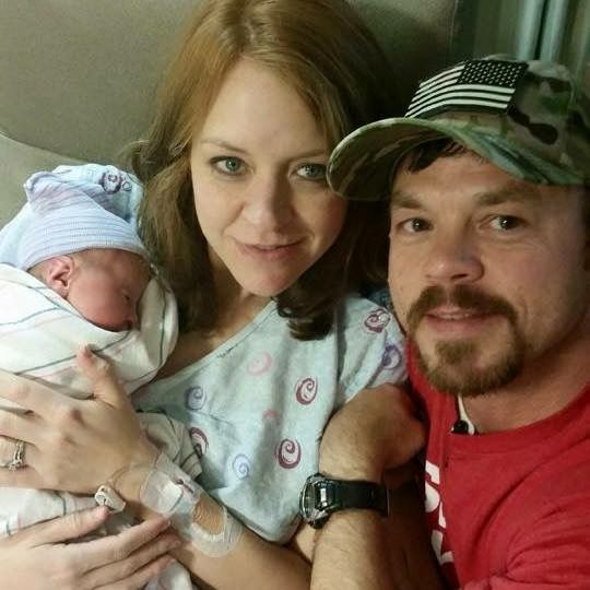 Proud Christian parents hold their new Baby who sleeps peacefully