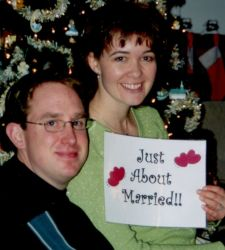 Christian singles sit together and smile while holding up a Just About Married sign