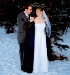 A handsome gentleman wraps a coat around a pretty woman in a white dress in the winter