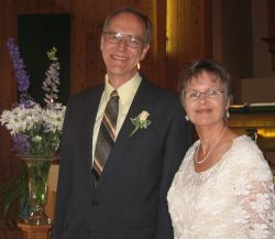Dave and Patricia smile in front of beautiful flowers on their wedding day