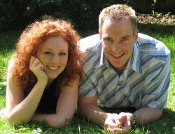 Cute Christian couple giggle together on the grass in the sunshine