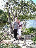 A man hugs a woman in a garden by a lake