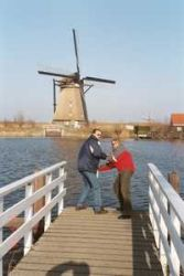 A man pretends to jump off a dock while his wife pretends to hold him back