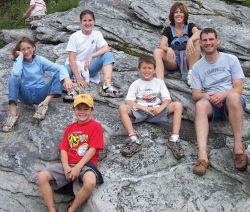 The whole clan sitting on rocks on a hike