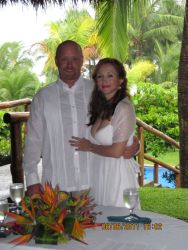 A beautiful Colombian Christian woman hugs her American husband at a tropical wedding