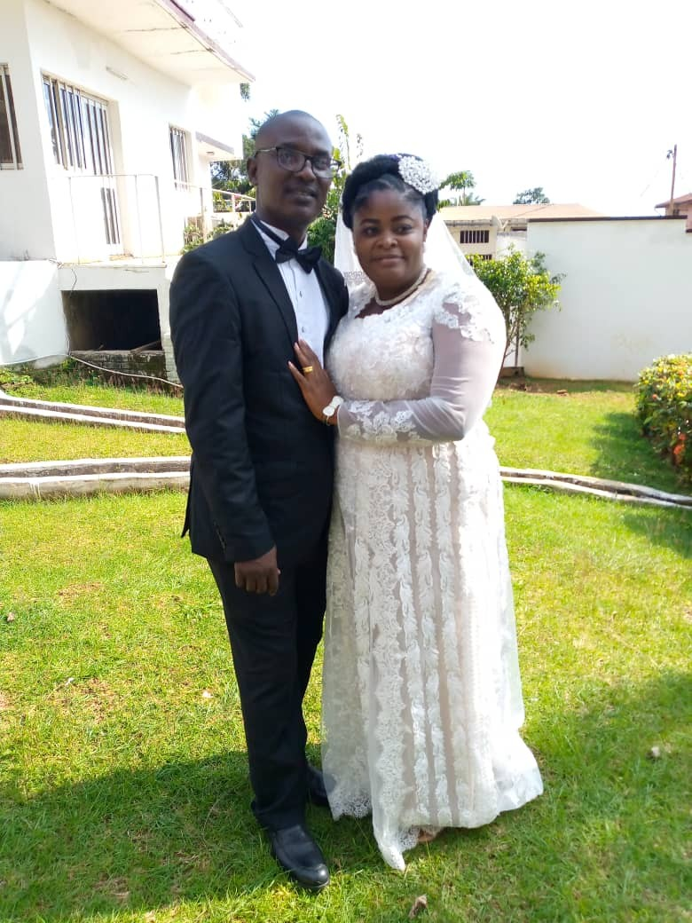African Christian couple standing on grass and smiling
