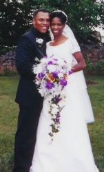 A cute Christian couple full of smiles on their wedding day as she holds beautiful flowers