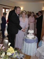 Christian couple smiles as they cut their wedding cake