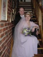 Beautiful wedding cress and veil on display as happy bride and groom pose together on the stairs