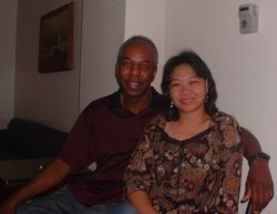 An interracial Christian couple site arm in arm on the couch