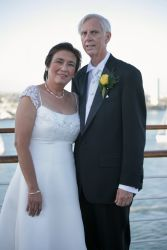 Older single Christians pose next to the water after marrying