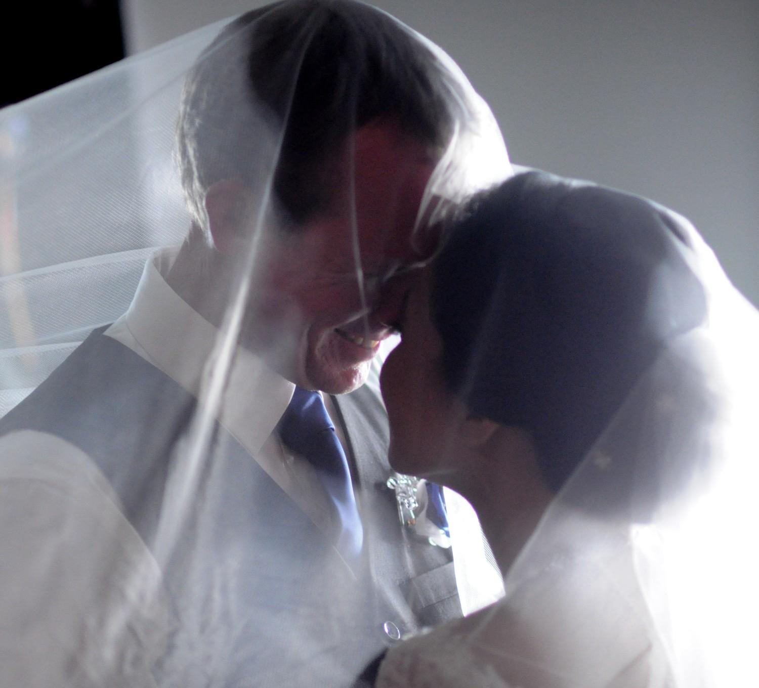 Australian Christian single marries beautiful Filipina who gazes at him with wedding veil covering them both