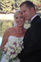 A California Christian woman with a beautiful smile leans in to cuddle with her husband on her wedding day